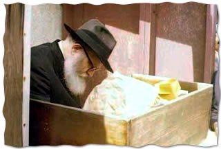 """Le Rabbi lisant les centaines de """"Pan"""", demandes de bénédictions, auprès du Ohel de son beau-père, le Rabbi précédent"""
