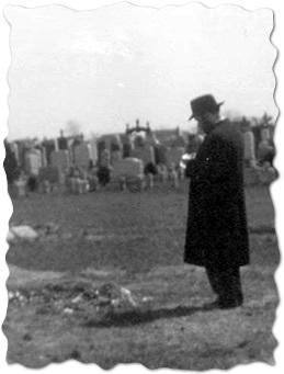 """Le Rabbi priant auprès de la sépulture de son beau-père, le Rabbi précédent, peu avant que l'on érige la pierre tombale et la structure du """"Ohel"""""""