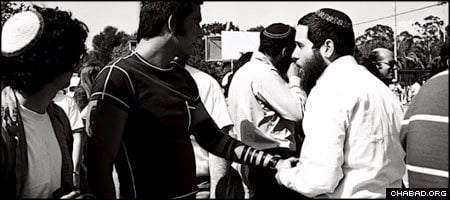 A young Rabbi Yossie Raichik assists Jewish men in donning tefillin during a Jewish pride rally in Los Angeles during the 1960s. (Photo courtesy Chabad of the West Coast)