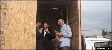 Jewish residents of Manchester, England, grab a bite to eat in a mobile sukkah installed in the flatbed of a truck by the local Chabad House.