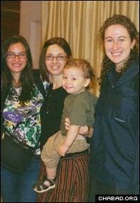 Rivkah Holtzberg holds her son Moshe (center).