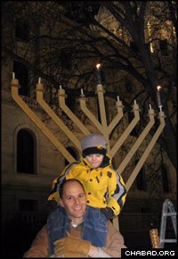 A father and son share a moment in front of a giant menorah at the Minnesota State House after a lighting ceremony coordinated by Chabad-Lubavitch.