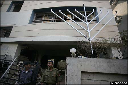 Indian police stand guard outside the Chabad House in Mumbai as the restored 25-foot Chanukah menorah greets passersby. The Chabad House was a study in contrasts, with blasted out walls juxtaposed against an apparently undamaged collection of the Holtzbergs' holy books.