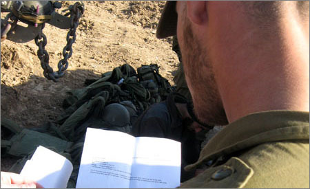 חייל מנצל את ההפוגה מהלחימה כדי לקרוא מכתב עידוד