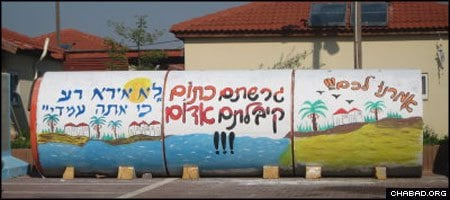 """Contrasting messages on a hastily-installed sewage pipe-cum-bomb shelter in Nitzan encapsulate the spirit of families removed from their Gaza Strip homes in 2006. Two words on the right translate to: """"We told you."""" On the left is a quote from the 23rd Psalm: """"I will fear no evil, for You are with me."""""""