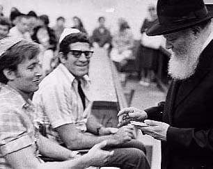 Le Rabbi s'entretient avec des anciens combattants blessés des Forces de Défense d'Israël et leur distribue des dollars à donner à la charité