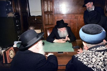 Rabbi Klein stands behind the Rebbe during an audience with the Israeli Chief Rabbis.
