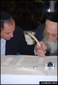 Ritual scribe Rabbi Moshe Klein, right, assists a celebrant in filling in one of the Torah's last letters.