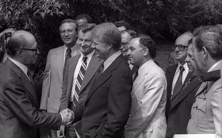 Prime Minister Menachem Begin and President Jimmy Carter shake hands, as Yehuda Avner (behind the President) looks on. (Photo: Ya'acov Sa'ar/Israel National Photos)
