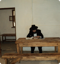 The author writing a prayer note before entering the resting place of the Baal Shem Tov in Mezhibush.