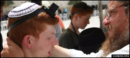 A participant on a summer Birthright Israel trip for people with special needs dons the Jewish prayer boxes known as tefillin at the Western Wall.