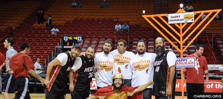 Chanukah celebrants enjoy a moment on the court before fans arrive for the Miami Heat's Dec. 1 face off against the Detroit Pistons at American Airlines Arena. (Photo: Mendy Bleier)