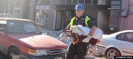 Det. Chris Bell rescues two Torah scrolls from the destroyed Chabad House in Christchurch, New Zealand.