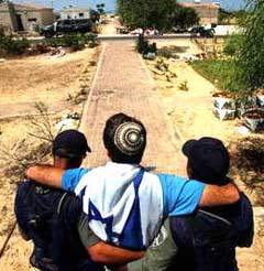 Israeli policemen remove a resident of the Jewish settlement Gadid in the Gaza Strip, August 19, 2005