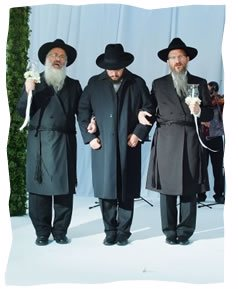 Under the Chuppa: Aizik Rosenfeld, flanked by his father Rabbi Yehoshua Binyomin, left, and his father-in-law, Rabbi Berel Lazar.