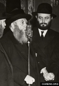 With his son-in-law and future successor by his side, the Sixth Rebbe speaks at an event in the United States. (Photo: Lubavitch Archives)