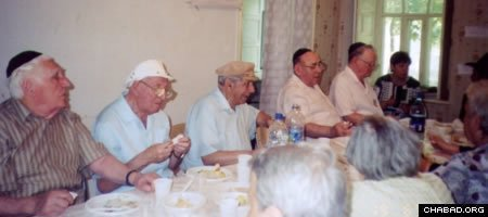 Elderly residents of Makeyevka, Ukraine, enjoy a kosher meal and Jewish inspiration at the home of Chief Rabbi Eliyahu and Dassi Kramer.
