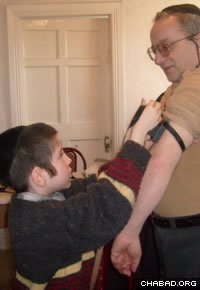 One of the Kramers' children helps a Jewish man don tefillin.