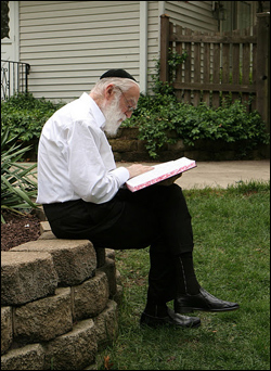 My grandfather studying the Talmud in our backyard .