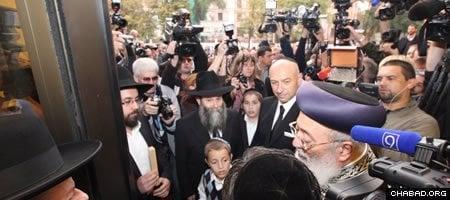 Rabbi Shmuel Kamenetzki and philanthropist Gennady Bogolubov, center, await the affixing of a mezuzah to the entrance of the new Menorah Center by Israeli Chief Rabbi Shlomo Amar. (Photo: djc.com.ua)