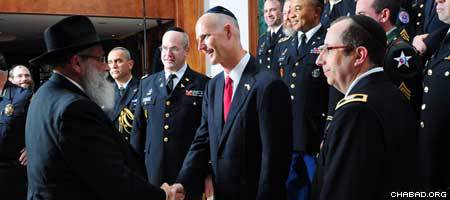 Florida's Gov. Rick Scott being greeted by Rabbi Shalom Ber Lipskar, director of the Aleph Institute, at the Military Chaplain Training Program.