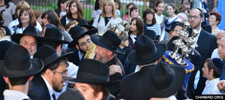 Benzion Chanowitz, center, celebrates the receiving of the Torah provided to the Chabad-Lubavitch Jewish Center of Marion County, Fla.