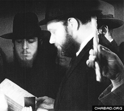 The Lubavitcher Rebbe seving as mesader kiddushin, officiating at the wedding of Rabbi Goldstein.