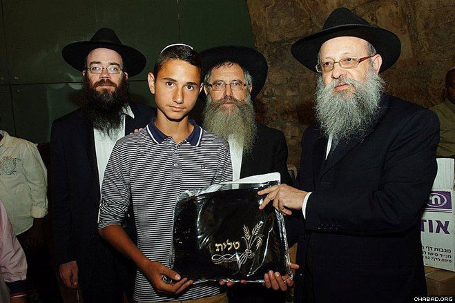 A tallis and a pair of tefillin are provided to every boy. Presented here by Rabbi Yitzchok Hazan, right, director of Chabad-Lubavitch in Rome, who spearheads the annual celebration