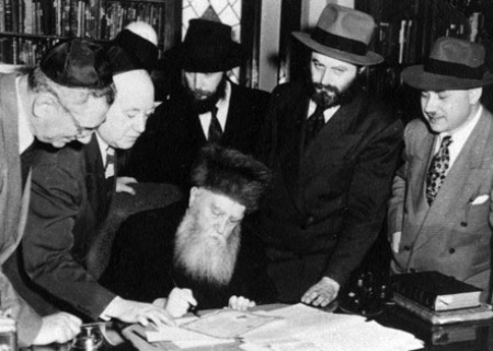 Rabbi Menachem Mendel (second from right) watches as his father-in-law signs his U.S. citizenship papers, New York, March 17, 1949.