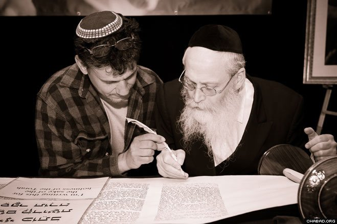 A local member of the Jewish community assists in writing a final letter of the Torah scroll—an ancient custom—with Rabbi Moshe Klein, an expert ritual scribe from Brooklyn, N.Y.