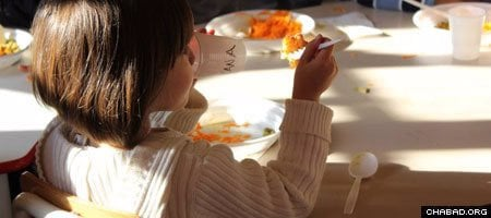 A young student enjoys a meal at Merkos Schools. Its kitchen will now also be used to prepare kosher food deliveries for those in need.