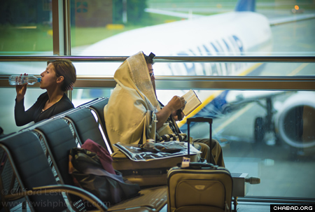 A man in prayer while awaiting a flight (Photo: Clifford Lester)