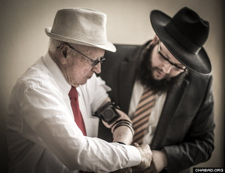 Rabbi Stambler assists in donning tefillin (Photo: Clifford Lester)