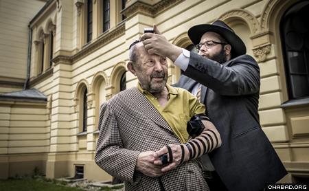 Rabbi Stambler helps an elderly man in Warsaw don tefillin (Photo: Clifford Lester)