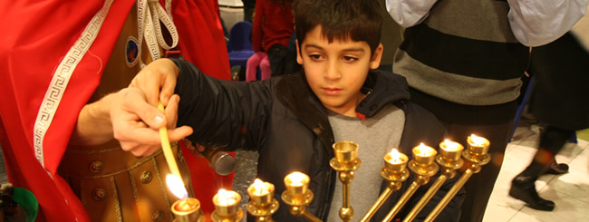Kid Lighting Menorah (650x245)