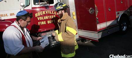 Tenenbaum assists Lenny Chornock, deputy fire chief of the Rockville Volunteer Fire Department, don tefillin. (Photo: Marc Asnin)