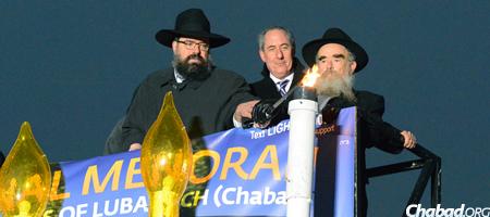 Rabbi Levi Shemtov (left), U.S. Trade Representative Michael Froman and Rabbi Abraham Shemtov igniting the National Menorah. (Photo: Judah Lifschitz)