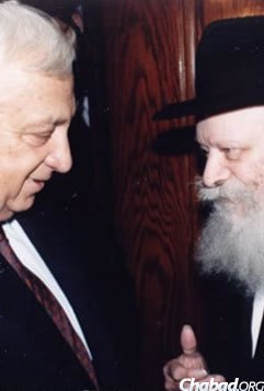 Ariel Sharon, receiving a dollar and a blessing from the Rebbe in 1989, during his service as Israel's Minister for Trade and Industry. (Photo: Chaim B. Halberstam/The Living Archive/JEM)