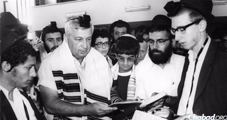 Sharon is called to the Torah in Kfar Chabad at the bar mitzvah of his son Omri, center.