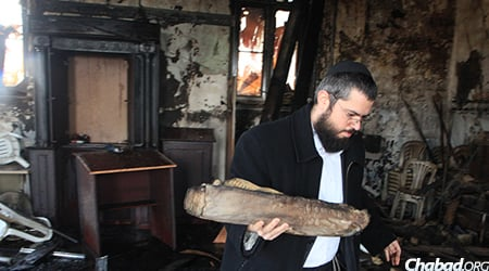 Rabbi Yitzchak Kofman, clearing away the ruins from the recent fire at the 500-year-old Great Choral Synagogue in Grodno, Belarus.