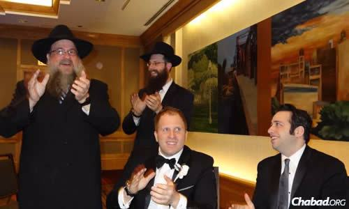 A beloved congregational rabbi, Moscowitz celebrates at a wedding along with his son, Rabbi Meir Moscowitz, center.