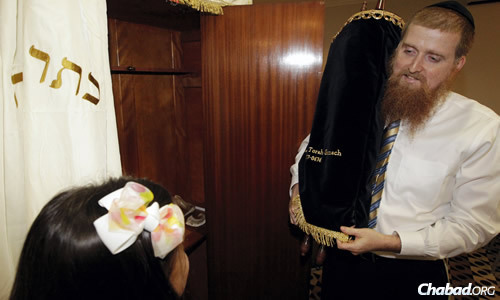 Rabbi Yitzchok Schmukler, co-director of Chabad of the Bay Area with his wife, Malky, stands in front of the aron kodesh, or Holy Ark, with the Torah he received on long-term loan, as his daughter Mushkie looks on. (Photo: KEVIN M. COX/The Galveston County Daily News)