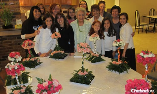 The Jewish Women's Circle, led by Malky Schmukler (first row, third from left), displays the flower arrangements they made in honor of Shavuot.