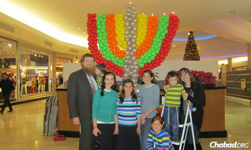 The Schmukler family gathers in front of a balloon menorah at a local mall during Chanukah.