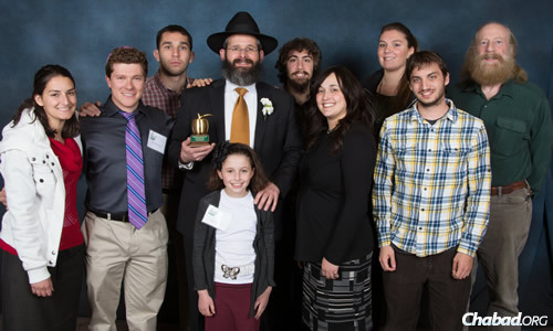 Gorelik surrounded by family, friends and students, specifically his wife, Devorah Leah; his daughter Basya; and, far right, professor H.J. Siegel; and to the left, Chabad student group president Michael Lichtbach (purple tie) and vice president/incoming president Danielle Geller (red shirt). (Photo: Colorado State University Alumni Association)