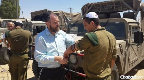 Chabad Terror Victims Project volunteers help Israeli soldiers don tefillin.
