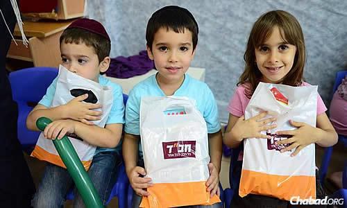 Children in Sderot, close to the Gazan border and showered by rocket attacks, clutch activity bags handed out by representatives of the Chabad Victims Terror Project. (Photo: Meir Alfasi)