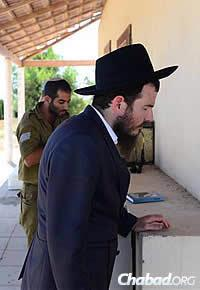 Chabad Rabbi Chaim Nochum Cunin, visiting from Chabad West Coast Headquarters in Los Angeles, prays with a soldier. (Photo: Meir Alfasi)