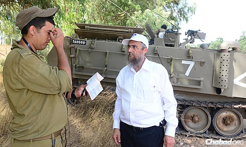 Rabbi Aharon Prus of Tzerei Agudat Chabad Headquarters Israel in Kfar Chabad, Israel, offers support to Israeli soldiers near the border with Gaza.
