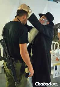 Rabbi Menashe Perman, director of Chabad of Chile, helps a soldier don tefillin. (Photo: CTVP)